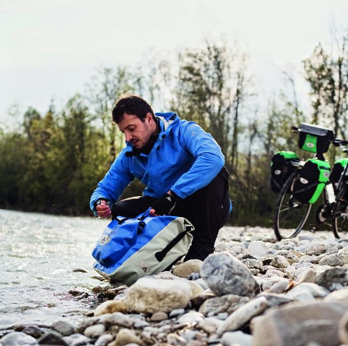 Cycliste qui lave ses sacoches de randonnée étanches
